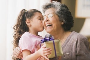 Hispanic granddaughter kissing grandmother and holding gift